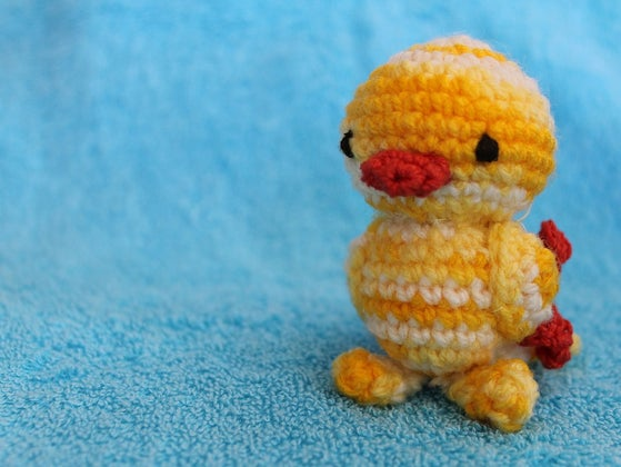 Small crocheted chick on blue background