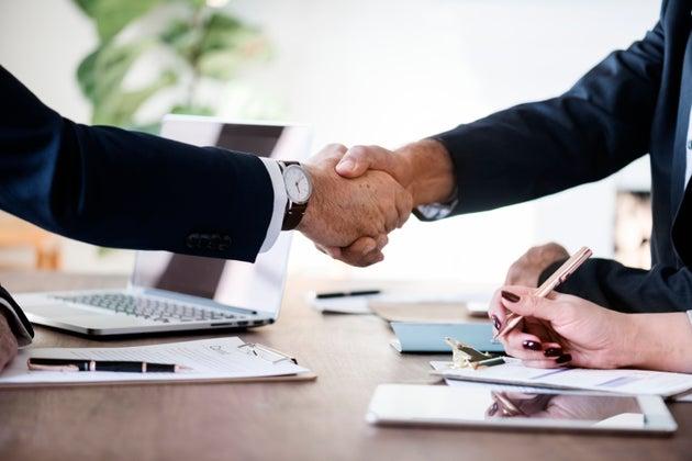 Two men shaking hands across a desk