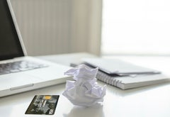 A desktop with an open laptop, a crumpled piece of paper and a credit card.