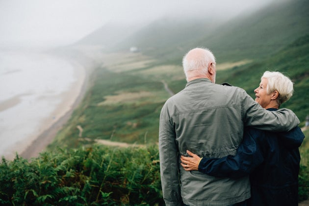 Older couple holding each other while overlooking a valley.