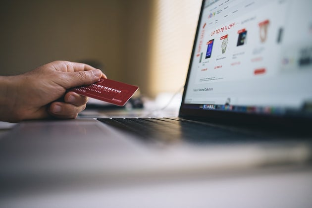 Person holding a credit card while shopping online