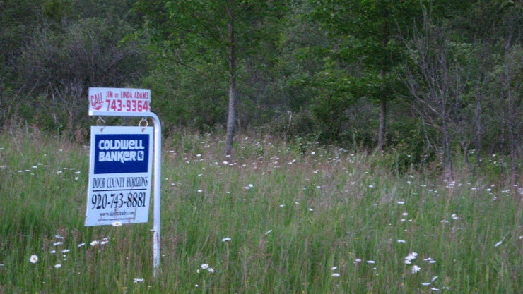 """Land with a """"For Sale"""" sign in front of it"""