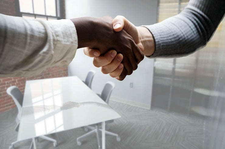 Two shaking hands in a boardroom