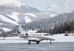 A small jet parked on an icy runway with snowy mountains in the background.
