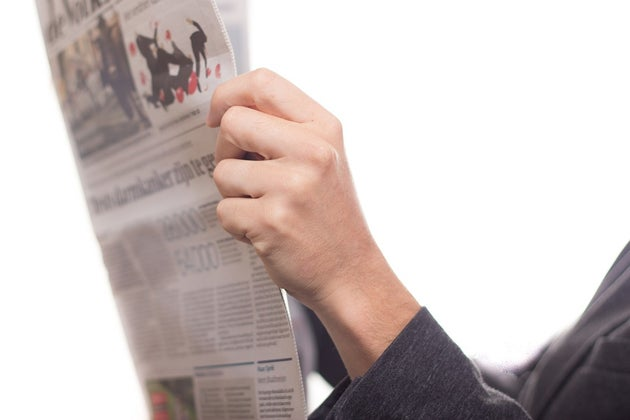 Hands holding an open newspaper